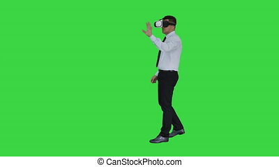 Young businessman using vr headset on a Green Screen, Chroma Key.
