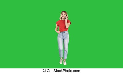 Woman in casual walking and talking on the phone on a Green Screen, Chroma Key.