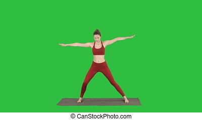 Woman practicing yoga, standing in Extended Side Angle exercise, Utthita parsvakonasana pose on a Green Screen, Chroma Key.