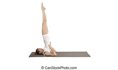 Woman practicing yoga, standing in salamba sarvangasana...