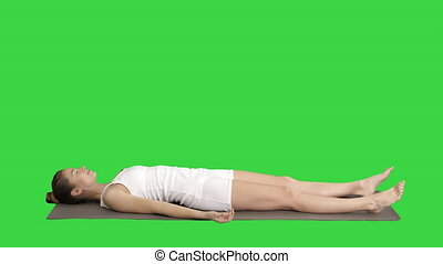 Yoga meditation laying on a mat with closed eyes on a Green...