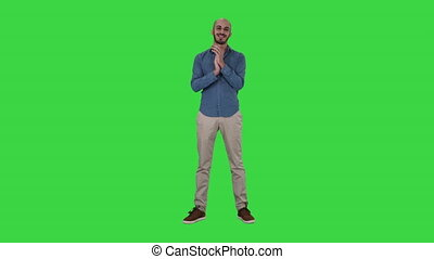 Young arabic man standing claps his hands smiling on a Green Screen, Chroma Key.