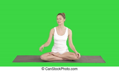 Young attractive woman sitting in lotus pose and pointing at...