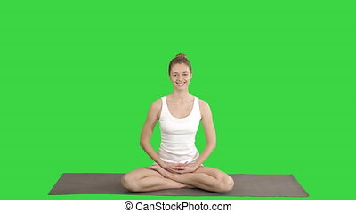 Young beautiful blonde woman doing yoga and smiling on a Green Screen, Chroma Key.