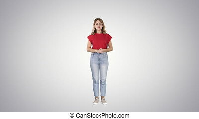 Young beautiful cute cheerful woman standing and looking at camera waiting for something on gradient background.
