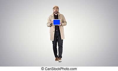 Young man walking, talking and showing digital tablet with blue screen mockup on gradient background.