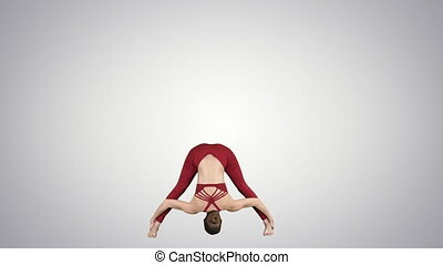 Young woman in forward bending asana yoga pose on gradient...