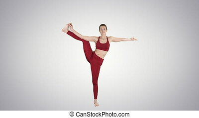 Young woman practicing yoga, standing in Utthita Hasta...
