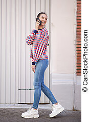 Full length side of happy young woman walking and talking with cellphone