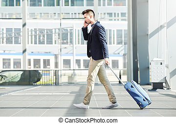 business man walking with luggage on telephone call at station