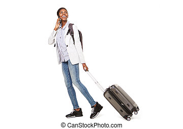 Full length side portrait of happy young black woman walking with suitcase and cellphone