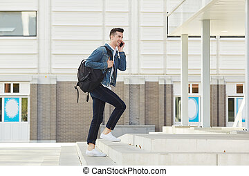 smiling man on telephone call with backpack outside