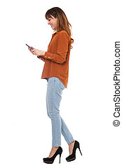 side portrait of young woman walking and looking at cellphone on isolated white background