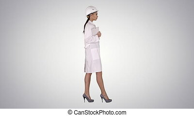 Attractive Hispanic woman in white lab coat and white safety hard hat walking holding notebook or tablet on gradient background.