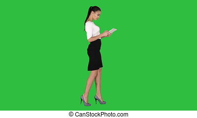 Beautiful young adult womann having fun playing game with tablet on a Green Screen, Chroma Key.