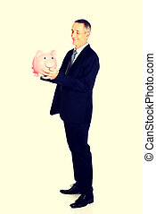 Full length side view businessman with piggybank