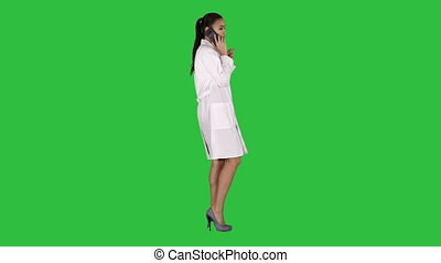 Female Dr smiles while talking on the phone, walking on a Green Screen, Chroma Key.