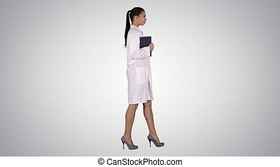 Happy smiling female doctor walking holding notebooks or...
