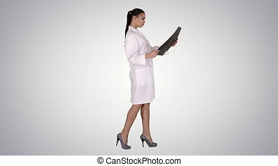 Full length side view. Intellectual woman healthcare personnel with white labcoat, looking at x-ray radiographic image, ct scan, mri on gradient background. Professional shot in 4K resolution. 013. You can use it e.g. in your commercial video, business, presentation, broadcast