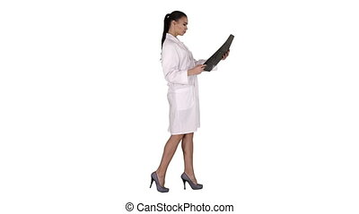 Full length side view. Intellectual woman healthcare personnel with white labcoat, looking at x-ray radiographic image, ct scan, mri on white background. Professional shot in 4K resolution. 013. You can use it e.g. in your commercial video, business, presentation, broadcast