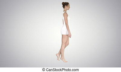 The young woman walking on her tip-toes on gradient...