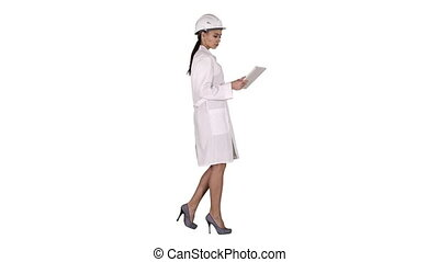 Young woman engineer walking with tablet looking at objects...