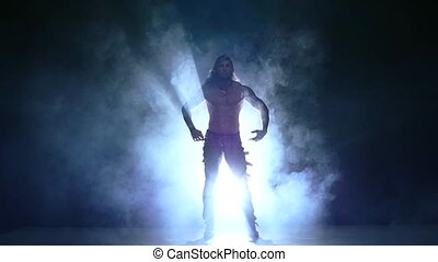 Full length silhouette of a young man dancer. Slow motion, smoke