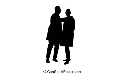 Silhouette Two doctors are making selfie using a smartphone and smiling.