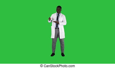 Smiling physician or medic presenting nasal spray on a Green...