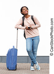 Full length smiling young african american woman standing with suitcase and mobile phone against white wall