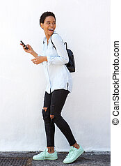 Full length smiling young woman walking with cellphone and bag