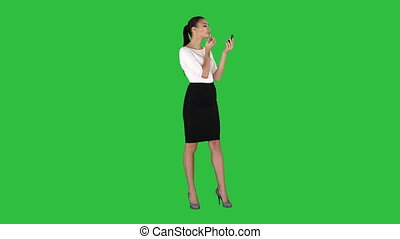 Beautiful woman, dyes her lips lipstick pink, looking in the mirror on a Green Screen, Chroma Key.