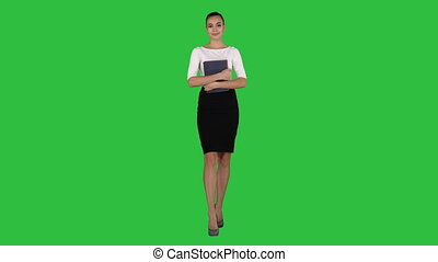 Beautiful young woman with notebooks walking on a Green Screen, Chroma Key.