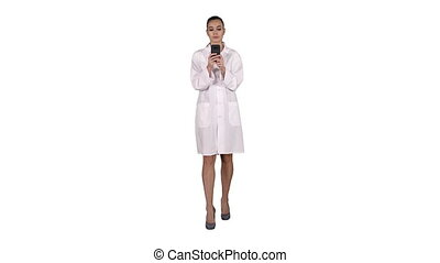 Cheerful cute young woman doctor typing text on phone while walking on white background.