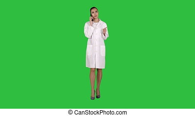Confident female doctor, healthcare professional talking on phone with patient on a Green Screen, Chroma Key.