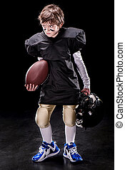 angry boy american football player holding rugby ball and helmet