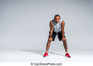 full length view of athletic young african american sportsman standing with hands on knees