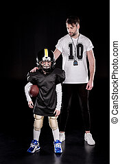 boy american football player standing with ball near coach