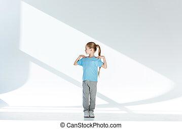 Full length view of happy little girl in sportswear exercising