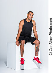 full length view of young african american sportsman sitting