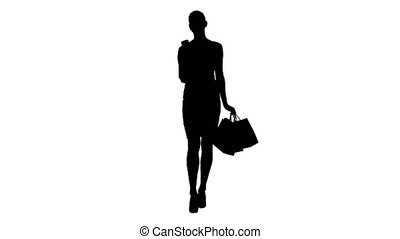 Silhouette Happy young woman with smartphone making picture of her shopping bags.