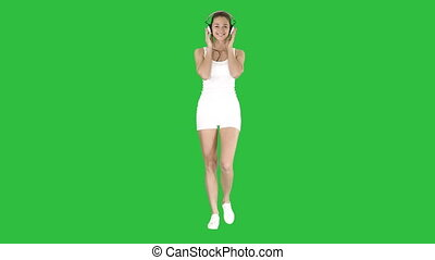 Sportswoman listening music in headphones on a Green Screen,...