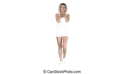 Sportswoman listening music in headphones on white...
