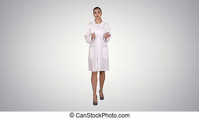 Woman doctor explaining and talking to camera while walking on gradient background.