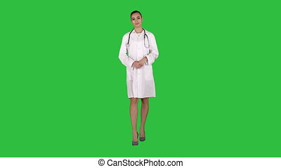 Young medical doctor woman presenting and showing product or text on a Green Screen, Chroma Key.