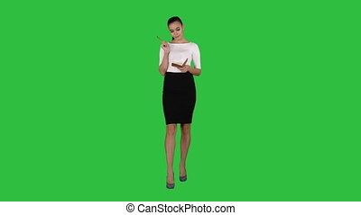 Young woman making notes while walking on a Green Screen, Chroma Key.