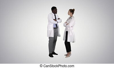 Woman and man doctors with crossed arms on gradient background.