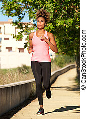 Full length young african woman running outdoors in morning