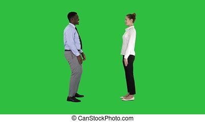 Young woman and young man in formal clothes give high five on a Green Screen, Chroma Key.