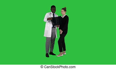 Young woman visiting radiologist for x-ray exam of her brain on a Green Screen, Chroma Key.